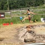 La femme participe à une course, la Spartan Race, sur un terrain accidenté.