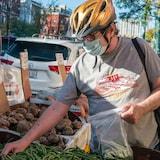 A shopper rummages through vegetables in Toronto's Kensington Market on Oct. 19.