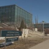"""Deux bâtiments reliés par une passerelle, avec une affiche à l'avant-plan où il est écrit, en anglais, """"Centre international de vaccins""""."""