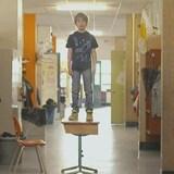 Un garçon est debout sur un pupitre dans le couloir d'une école.