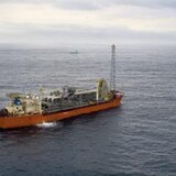 The SeaRose,a floating production, storage and offloading vessel, at sea. Platforms in background.