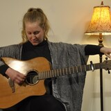 une femme assise, accorde sa guitare.