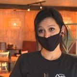 سيّدة تضع كمامة واقفة داخل مطعم.