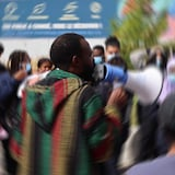 Un manifestant muni d'un porte-voix s'adresse à des adolescents.