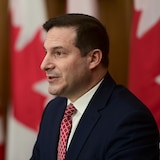 Le ministre de l'Immigration, vêtu d'un veston et d'une cravate, parle dans un micro devant des drapeaux du Canada.
