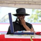 Martine Moïse, habillée en noir, porte une main à la bouche devant un cercueil recouvert d'un drapeau haïtien.