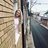Marylene Levesque a le haut du corps sorti d'une fenêtre, et la vue derrière elle est une rue de la basse-ville de Québec. Elle a les cheveux blonds et est souriante.