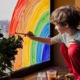 une petit garçon peint un arc-en-ciel sur une vitre.