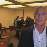 Michel St-Amant s'adresse à un journaliste, des parents discutent derrière lui,