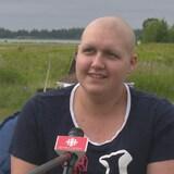 Un micro de Radio-Canada est tendu vers Noémie qui répond à une question alors qu'elle se trouve dans un champ.