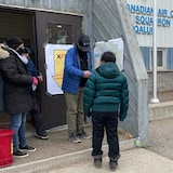 People gather outside a polling station.
