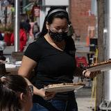Isang babae na nagse-serve ng pizza sa mga kostumer ng restaurant.