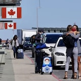 people hug outside of the Ottawa airport June 16, 2021.
