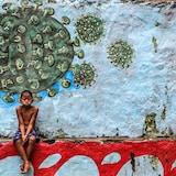 Un jeune garçon assis devant une murale représentant le coronavirus.