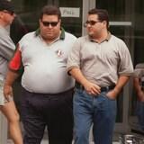 Deux hommes marchent sur un trottoir