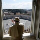 Un homme fait la bénédiction devant une grande fenêtre.