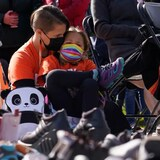 A woman and her daughter sit behind a display of children's shoes during the National Day for Truth and Reconciliation in Ottawa on Thursday, Sept. 30, 2021.