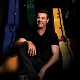Portrait de Roch Voisine assis au milieu d'étuis de guitare.