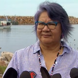 RoseAnne Archibald, the national chief of the Assembly of First Nations, criticized DFO's enforcement Thursday of the Sipekne'katik treaty fishery. She is speaking to the reporters on the docks, with water and boats in the background.