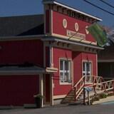 On voit un bâtiment sur lequel sont accrochés trois drapeaux. Deux drapeaux de la municipalité de Saint-Ulric et un drapeau du Québec.