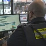 Un agent des services frontaliers travaillant à l'ordinateur, vu de dos.