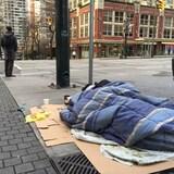 Un homme est enveloppé dans un sac de couchage posé sur des morceaux de carton sur le trottoir et tente de dormir, alors que derrière lui un piéton attend de traverser une intersection.