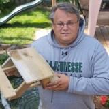 Un homme présente une petite table de pique-nique en bois. Il porte des lunettes et un chandail à capuche. Il pose dans son jardin.