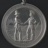 Une médaille sur laquelle sont gravés un chef autochtone et un officier britannique se serrant la main.