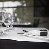 Des verres, une salière, une poivrière et des ustensiles sont disposés sur une table.