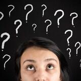 Une jeune femme confuse et des points d'interrogation