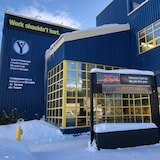 """Front view of theThe Yukon Workers' Compensation Health and Safety Board building. It is winter, with snow on the ground, on the roof and window ledges. The board holds a digital count of accidents in the workplace near the entrance of the building which says """"254 Yukoners hurt on the job this year"""","""