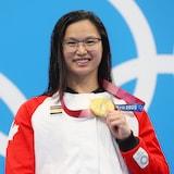Una joven muestra su medalla de oro en los Juegos de Tokio.