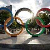 Les cinq anneaux olympiques avec un rayon de soleil en plein milieu
