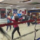 Sauts-papillons et course sur place, des jeunes du club de boxe Underground Gym se réchauffent.