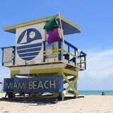 Le soleil brille sur la plage de sable blond et la mer turquoise.