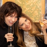 Les deux femmes sont vues très souriantes, un verre de mousseux à la main.