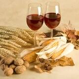 Des épis de maïs et des verres de vin rouge disposés sur une table.