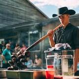 un jeune homme avec un chapeau de cowboy fait griller des steaks au barbecue avec une fourche