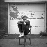 L'uteur-compositeur-interprète, guitariste et photographe Jérémy Lachance. assis sur une chaise.