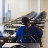 Une femme travaille sur son ordinateur, assise à une table, dans un couloir où il n'y a personne d'autre.