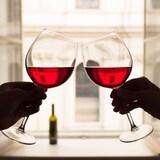 Deux personnes lèvent un toast avec leurs coupes de vin rouge.