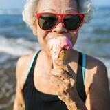 Une femme d'âge mûr mange une crème glacée sur le bord de la plage.