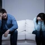 Vue sur un sofa, où l'on voit un homme et une femme en position recroquevillée, la tête dans les mains.