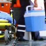 Un ambulancier porte une glacière bleue pour un don d'organes. Une civière se trouve en avant-plan.