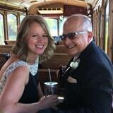 Un couple souriant assis dans un wagon de train antique, un verre à la main