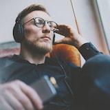 Un bel homme barbu portant des lunettes est assis et écoute attentivement de la musique avec des gros écouteurs.