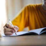 Une femme tient un stylo et écrit dans un cahier.