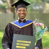 Un homme souriant habillé d'une toge et d'un mortier tenant dans ses mains un diplôme et des fleurs.