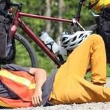 Un jeune homme couché par terre, devant son vélo.