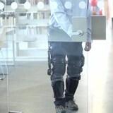 Un homme porte des prothèses intelligentes aux jambes et marche pour ouvrir une porte.